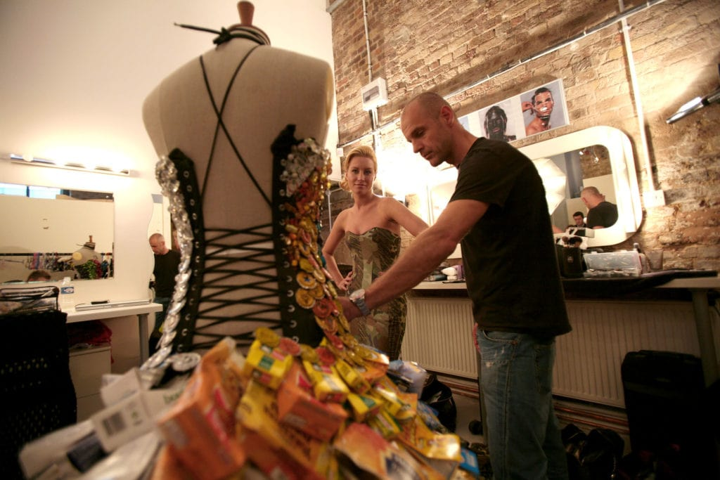 Man Showing A Woman A Dress Of Recycled Materials