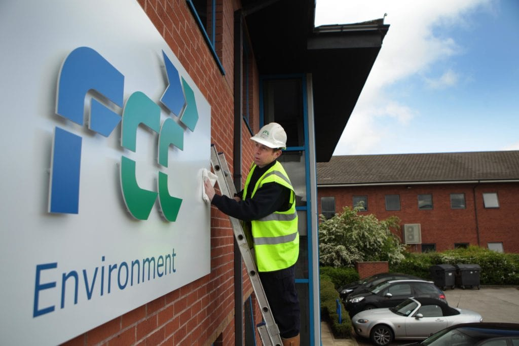 FCC Environment Logo Being Attached To A Building