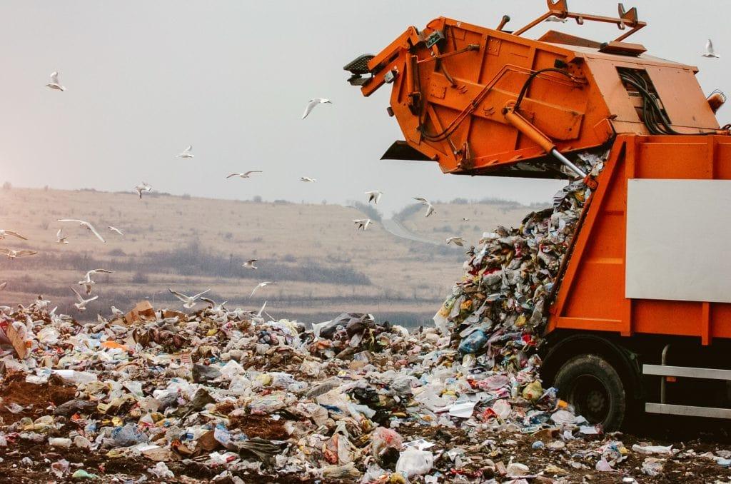 A Bin Truck Emptying Waste Into Landfill