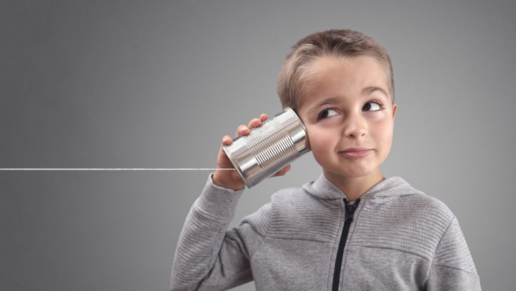 A Child Holding A Tin Can Phone To His Ear