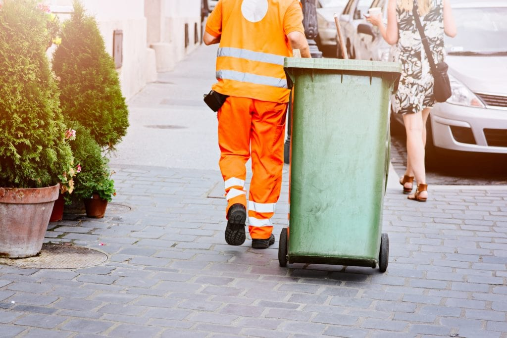 A Worker Moving A Wheelie Bin