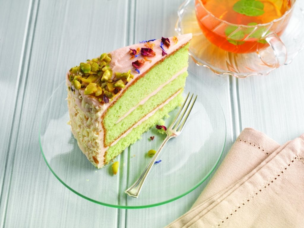 A Pistachio Rose Cake On A Clear Plate