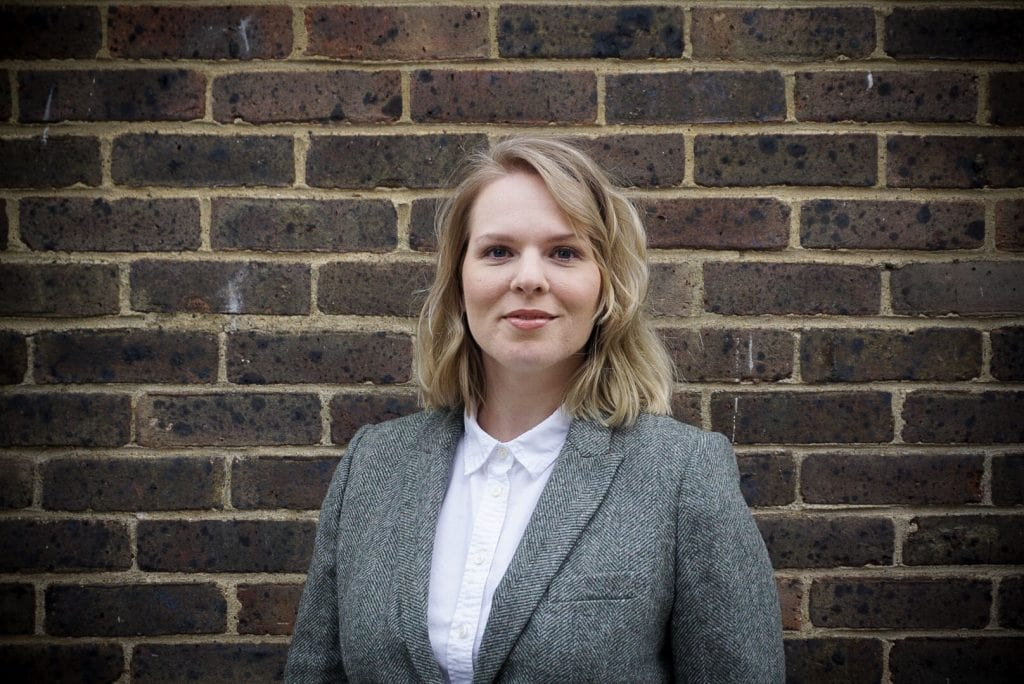 Julia Glotz Headshot In Front Of A Brick Wall