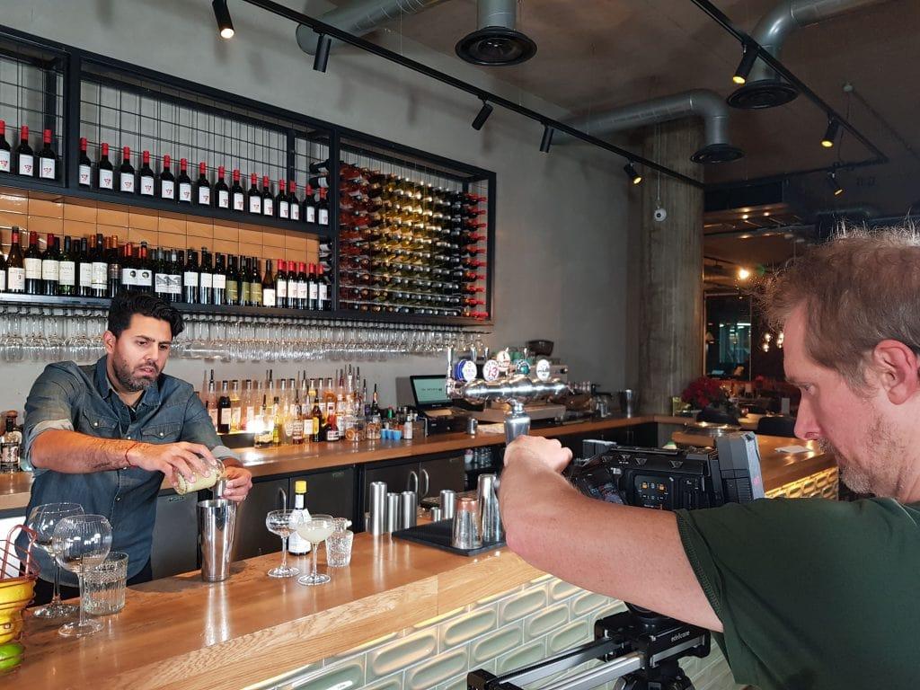 A Man Being Filmed Making Cocktails In A Bar