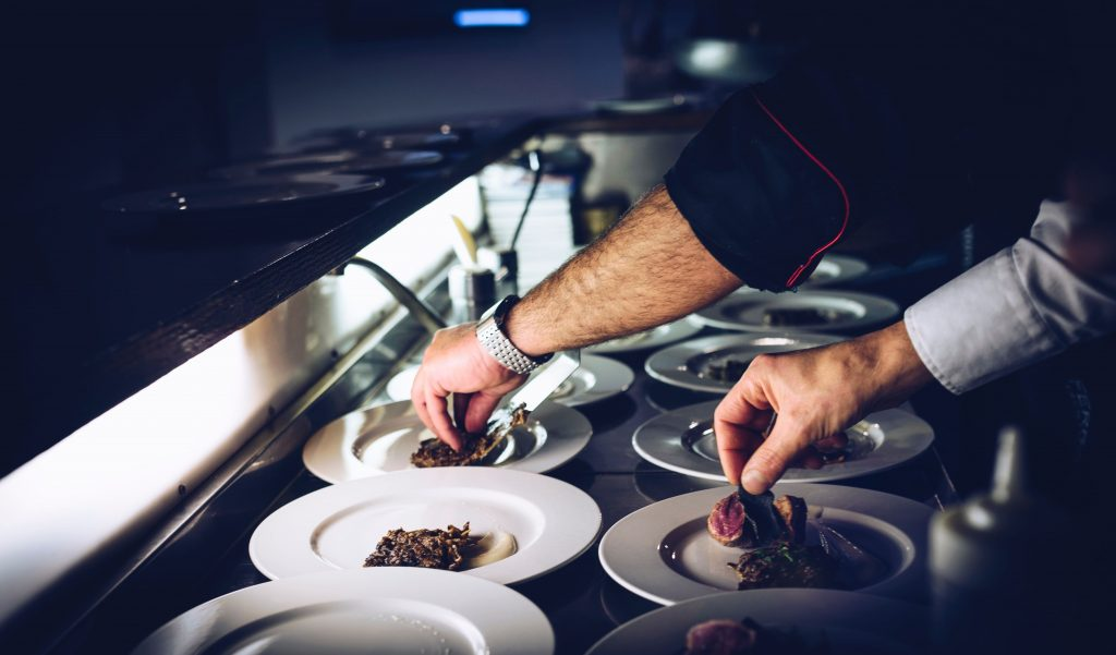 A Chef Adding Finishing Touches To A Range Of Dishes