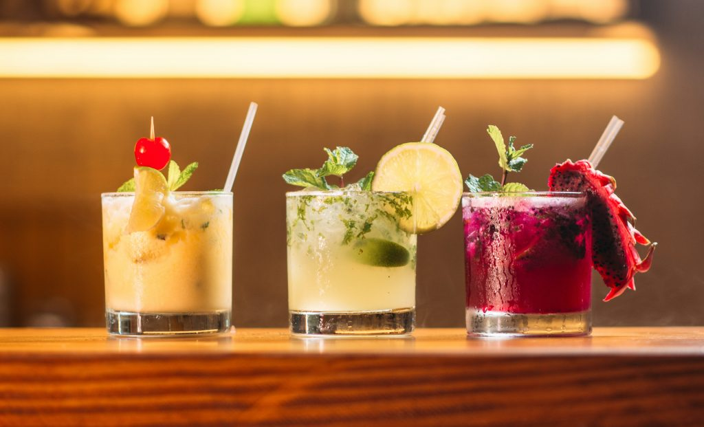 3 Different Coloured Cocktails On A Bar