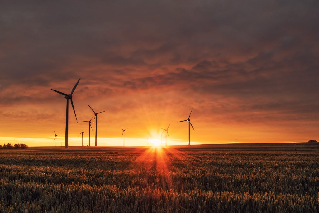 A Sun Setting Over A Field With Wind Turbines In The Background