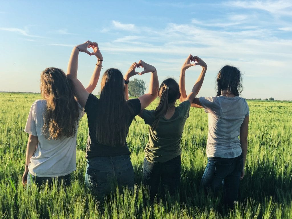 Four Women In A Field Making Heart Signs With Their Hands