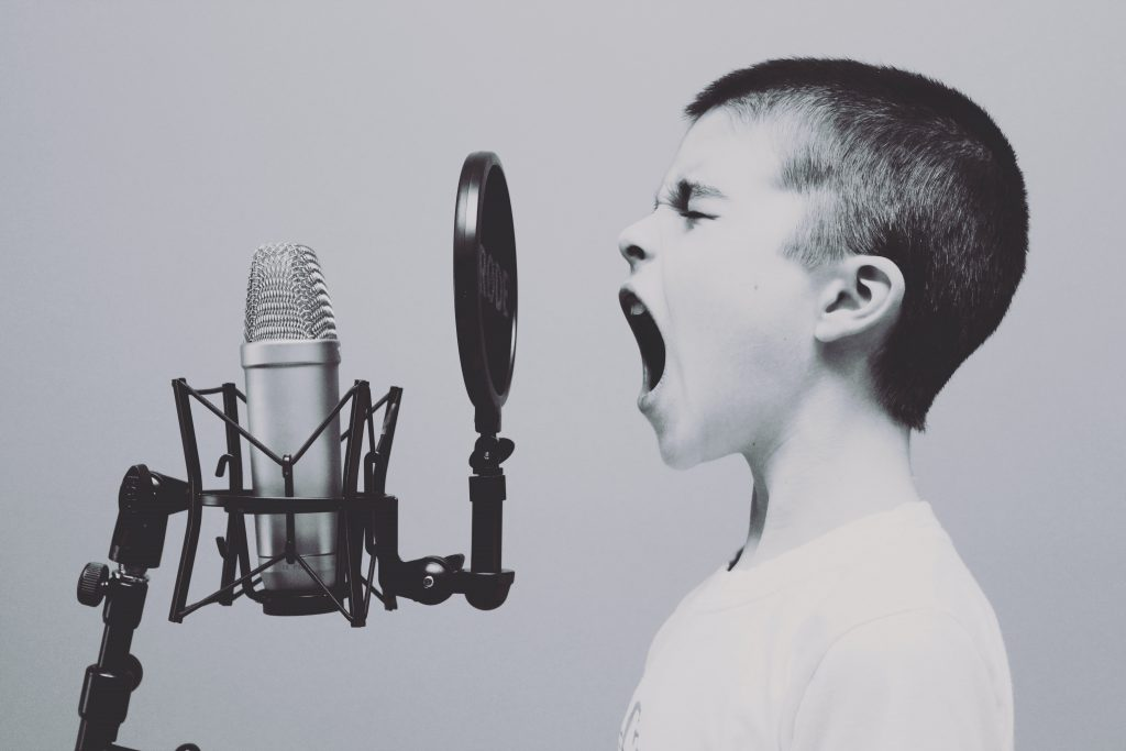 A Child Shouting Into A Microphone