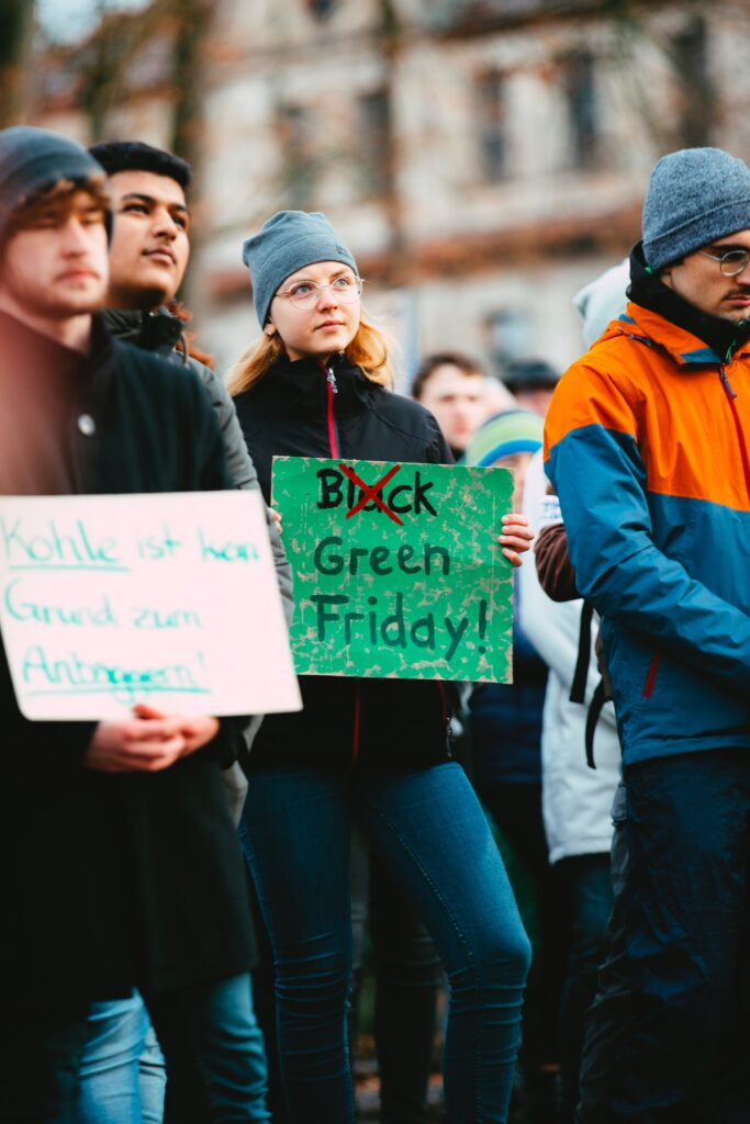A Group Of People Holding Black Friday Environmental Protest Signs