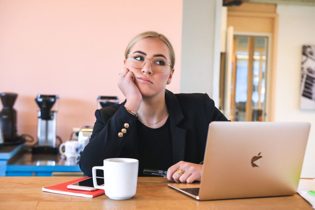 A Women Leaning On A Desk With A Laptop & A Coffee