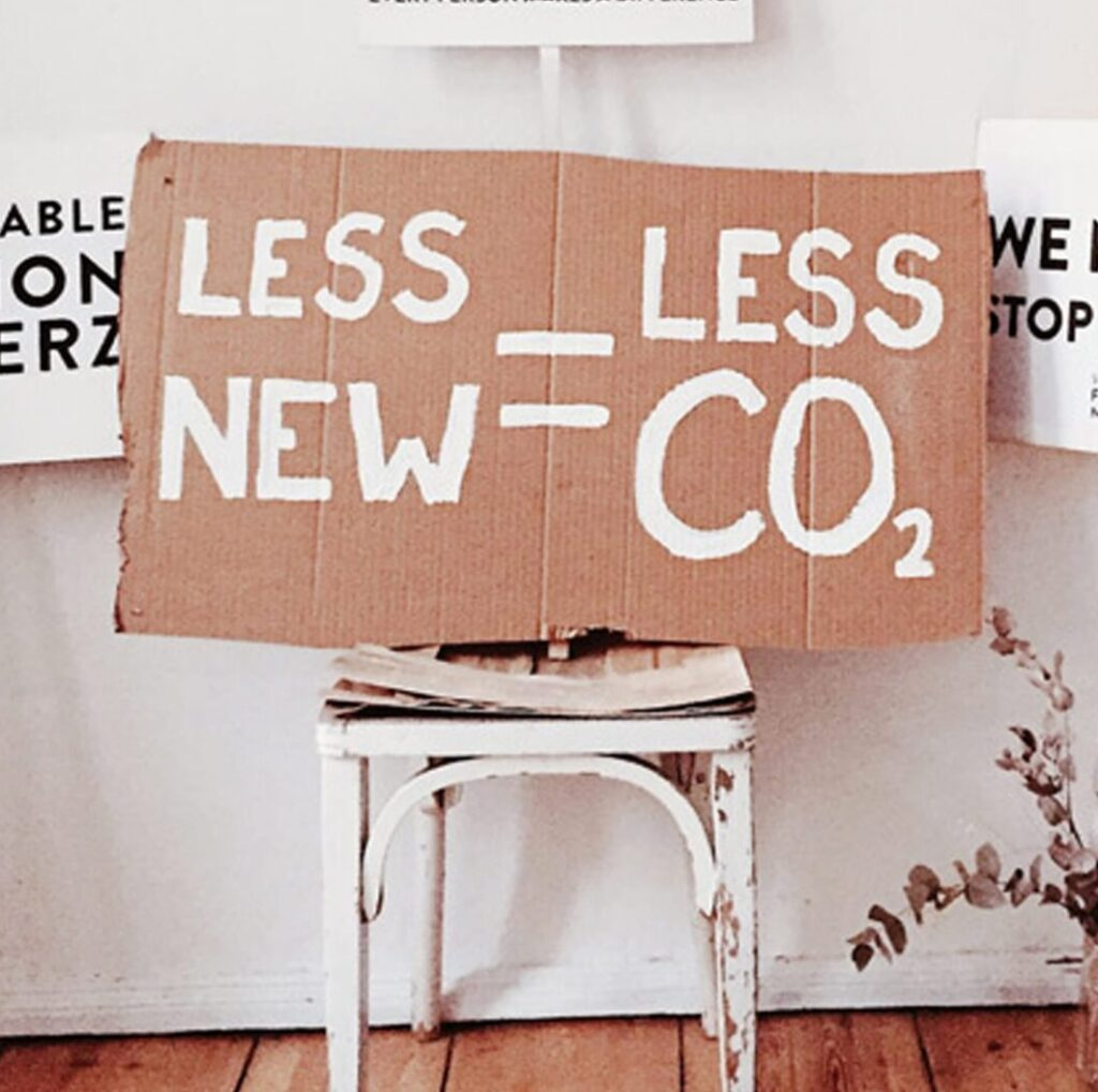 """Piece Of Cardboard On A Chair With """"Less New = Less CO2"""" Written On It"""