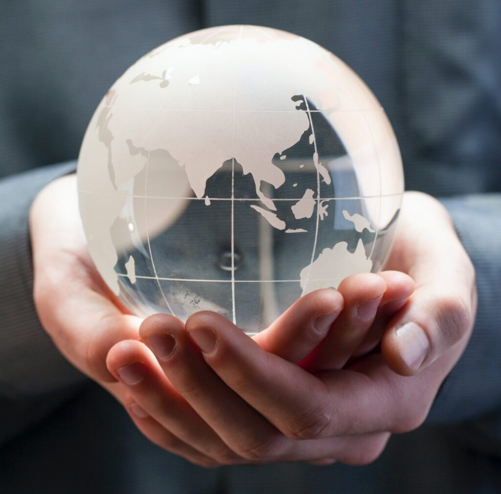 Two Hands Holding A Glass Globe