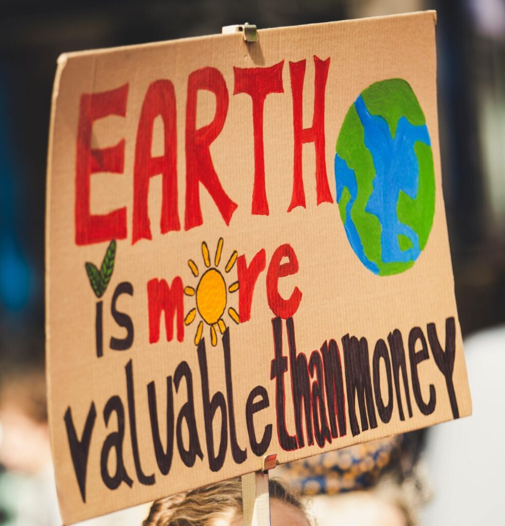 """An Environmental Protest Sign That Reads """"Earth Is More Valuable Than Money"""""""