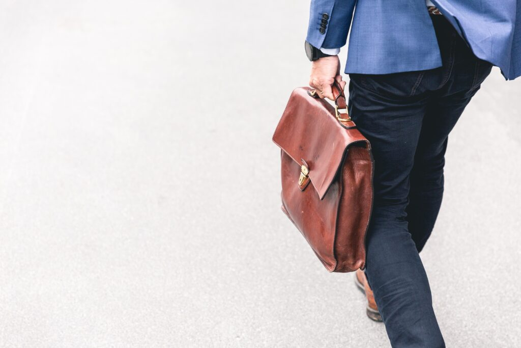 Person In Suit Holding A Brown Leather Bag
